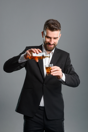 Businessman pouring whisky into glass