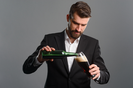Businessman pouring beer in glass Stock Photo