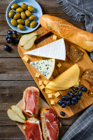 Ingredients for evening meal on wooden table. Juicy olives and grapes, jerky meat, pear halves, different types of cheese and baguette. Vertical still life, top view.