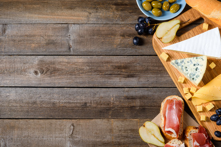 Bread, meat, cheese and fruits. Mouthwatering set of various food on wooden background. Big copy space for inserting your text. Stock Photo
