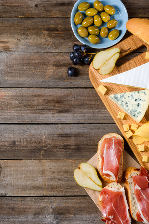 Foods for evening meal. Toasts with meat jerky, different types of cheeses, bread, grape, olive and pear halves on wooden table. Vertical still life with copy space.