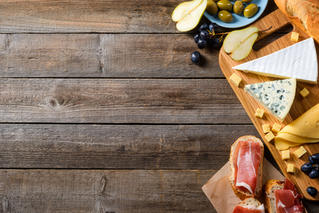 Fruits, cheese, meat and bread. Wooden tabletop in the background with space to insert your text or picture. Preparing for celebration.