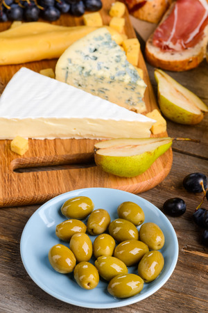 Italian cheeses, meat and fruits. Focus on a plate of green olives, grape, pear halves, cheese and toasts with jamon in blurred background. Cooking a delicious meal for lovers.