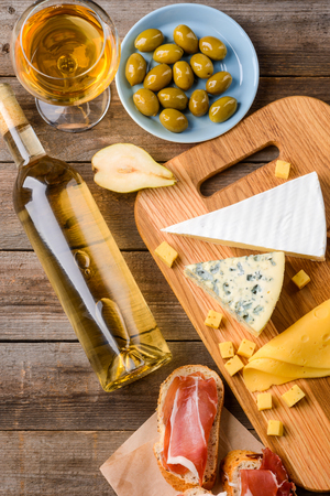 Wine snack set. A bottle and a glass of white wine, green olives, pear halves, toasts with meat jerky and few kinds of cheese: Roquefort, Brie, Cheddar and Parmesan. Vertical still life, top view.