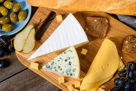 Different cheeses on cutting board