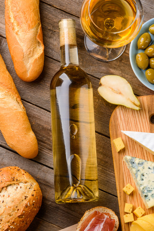 A bottle of white wine surrounded with three baguettes, a full wineglass, a plate of olives, a half of pear, a cutting board with cheese and jamon toasts on wooden background. A meal for gourmet.
