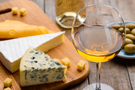 Cheese, olives and wineglass
