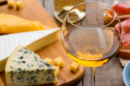 White wine and different cheeses Stock Photo