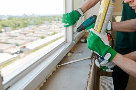 Travailleurs de la construction installant une fenêtre