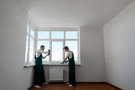 Two workers in the apartment Banco de Imagens