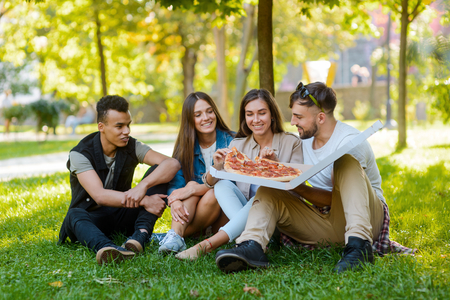 Friends enjoying a Salami pizza Фото со стока - 113219614