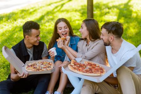 Girl feeding her friend pizza