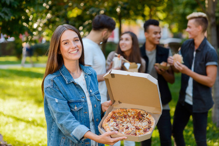 Girl holding box with pizza
