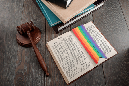 Judge's gavel and Exodus book of Bible with a rainbow bookmark. Ten commandments and LGBT marriage legalisation. 版權商用圖片 - 114699312