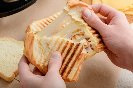Hands tearing a sandwich Stock Photo