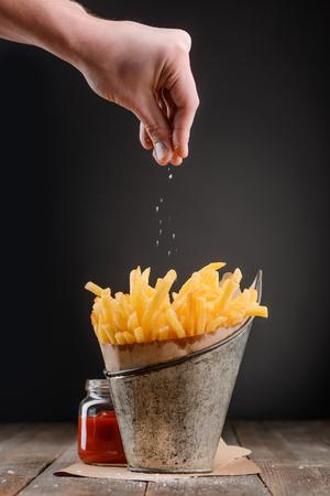 La main saupoudre une pincée de sel Banque d'images