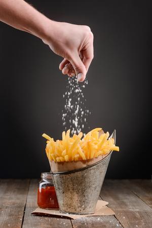 Hand adding a pinch of salt