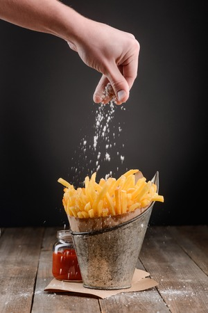 Hand sprinkles salt on fries