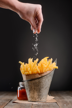 Hand sprinkles salt Reklamní fotografie