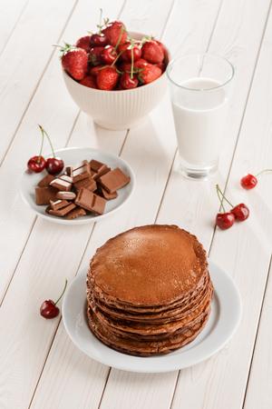 Pancakes, chocolate, berries and milk