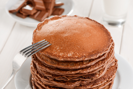 Fork on pile of pancakes Фото со стока