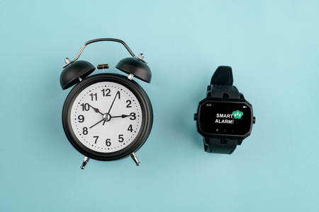 Analog alarm clock against watch Banco de Imagens