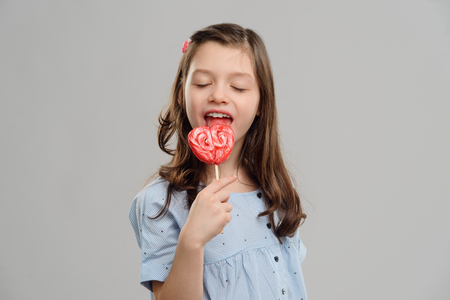 Girl licking heart shaped lollipop Banque d'images