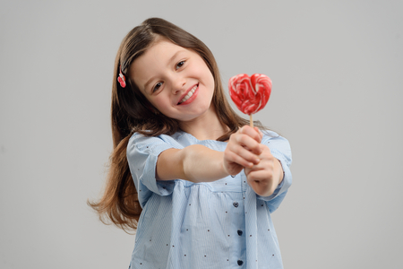 Child holding a pink lollipop