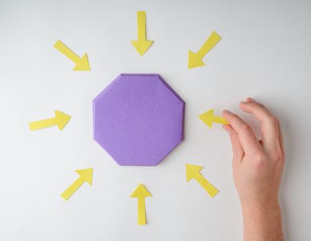 Hand putting arrows around octagon Stock Photo