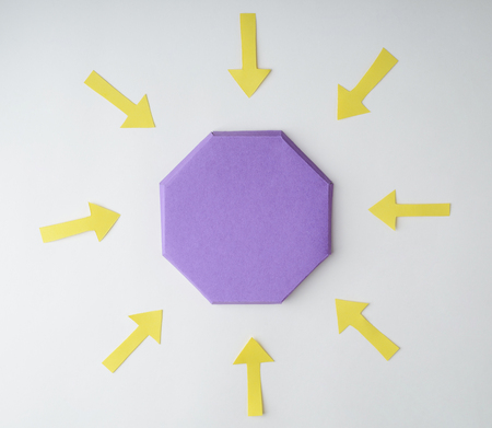 Violet octagon surrounded with yellow arrows on white background. Point to the center, focus concept. 스톡 콘텐츠