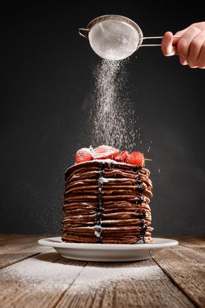 Icing sugar onto pancakes 版權商用圖片