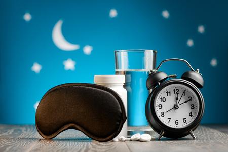 Eye mask, pills, alarm clock