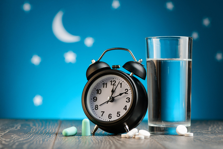 Clock, earplugs, pills and water Stok Fotoğraf
