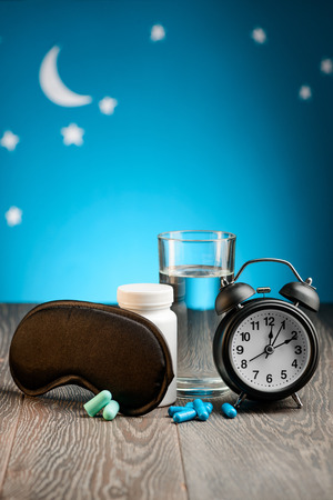 Mask, earplugs, pills and clock Stock Photo