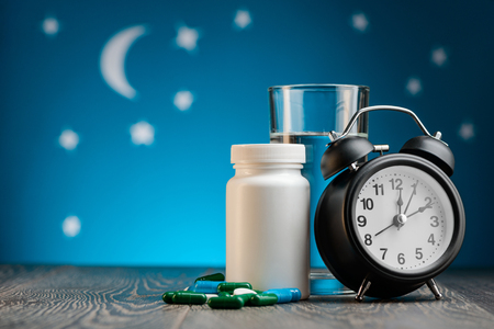 Sleeping pills, water and clock Stockfoto