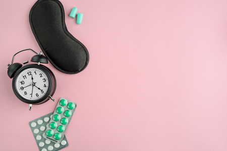 Alarm clock, eye mask, pills and earplugs on pink background with copy space. Bedtime accessories and medications for good sleep.