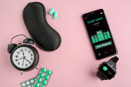 Alarm clock, eye mask, earplugs, pills, phone and watch on pink background. Sleep tracker apps and wearables.