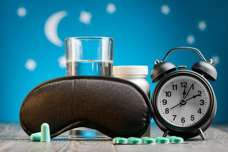 Earplugs, mask, pills and clock