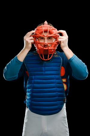 Catcher putting a mask on
