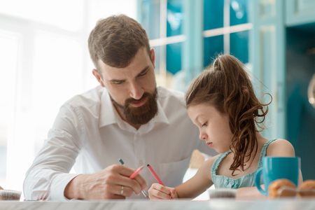 Dad helps daughter to draw