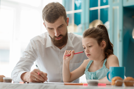 Father helps daughter with homework Stock Photo