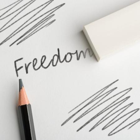 Eraser removing word Freedom Stock Photo