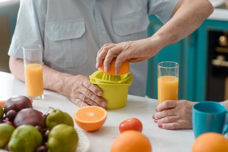 Old man squeezing an orange