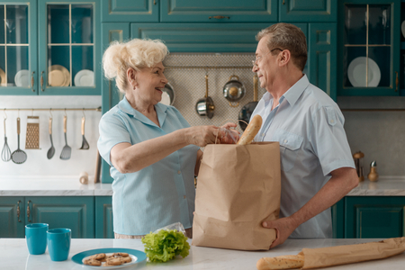 Senior couple taking groceries out