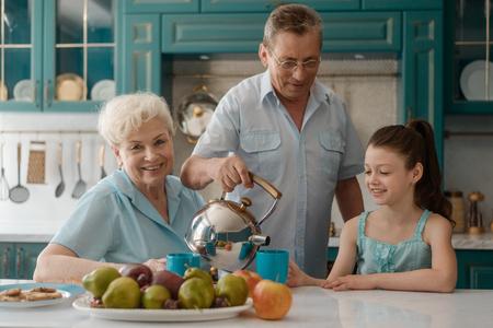 Grandad serving tea for granddaughter