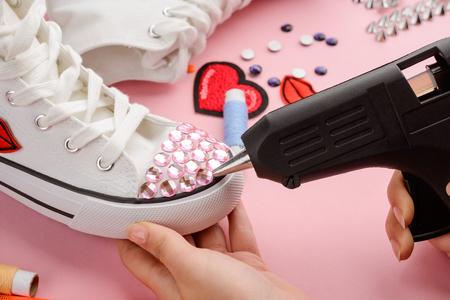 Applying pink rhinestones onto sneakers