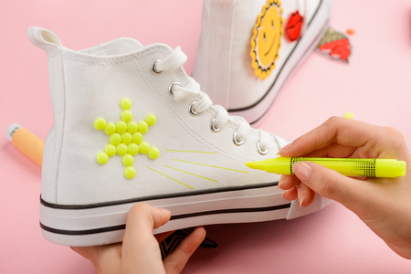 Girl drawing on a sneaker
