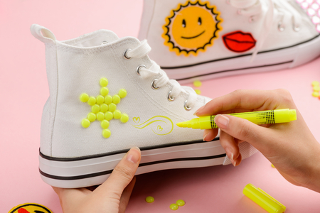 Girl drawing on white sneakers