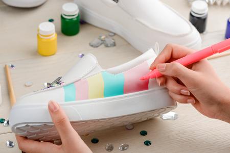 Girl painting white slip-on shoes Stockfoto