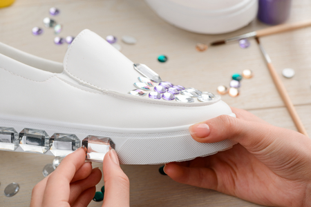 Girl decorates outsole of shoe